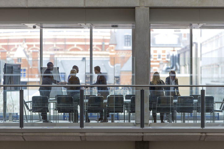 Group of six business people in a boardroom meeting. Shot at a distance from outside through the glass.